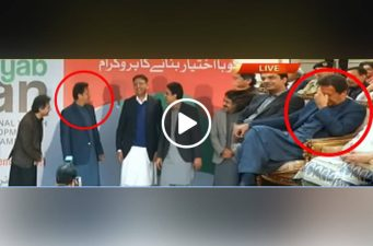 Imran Khan laughs shaking a hand with a guy